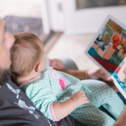 father reading book to infant